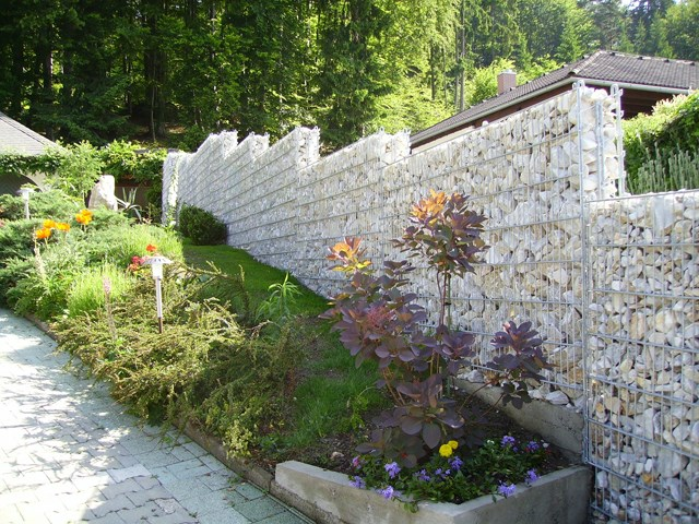 Kamena ograda Legi - Predstavlja vizuelnu i ujedno zvučnu barijeru, te ima jako široku primenu. Kombinacija sa manje primetnim žičanim  stubovima, ili jasnije naglašenim profilnim stubovima, rešetkastim panelom sa obe strane ograde i međusobnim povezivačima, čini čvrstu čeličnu konstrukciju, koja se ispunjava raznim vrstama i bojama kamena, formirajući izgled kamenog zida a bez potrebe za zidanjem. Kamena ograda se proizvodi u visinama 630-2430mm. Kombinuje se sa RM, R-S i ukrasnim panelima.